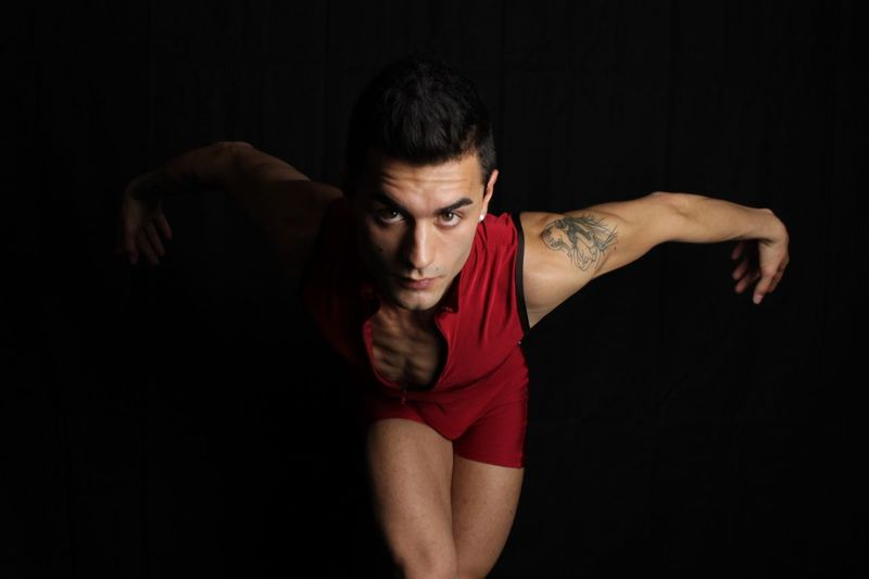 Portrait of young handsome man dancing with arms outstretched against black background