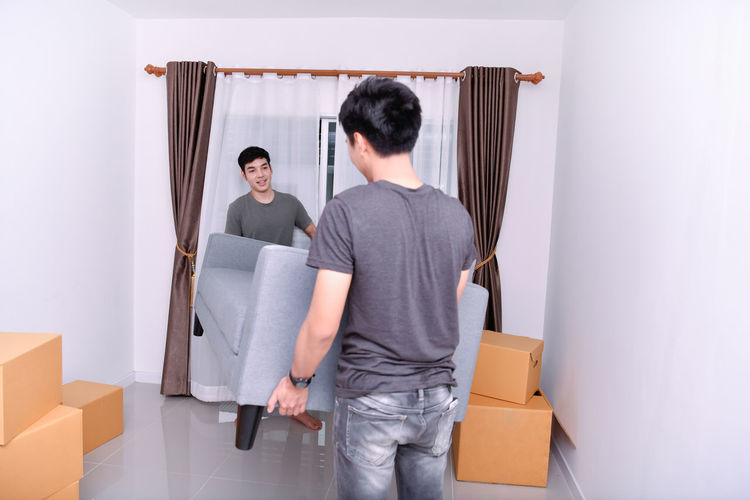 Adult Box Cardboard Casual Clothing Container Couple - Relationship Curtain Front View Holding Indoors  Jeans Lifestyles Men People Standing Three Quarter Length Two People Young Adult Young Men Young Women