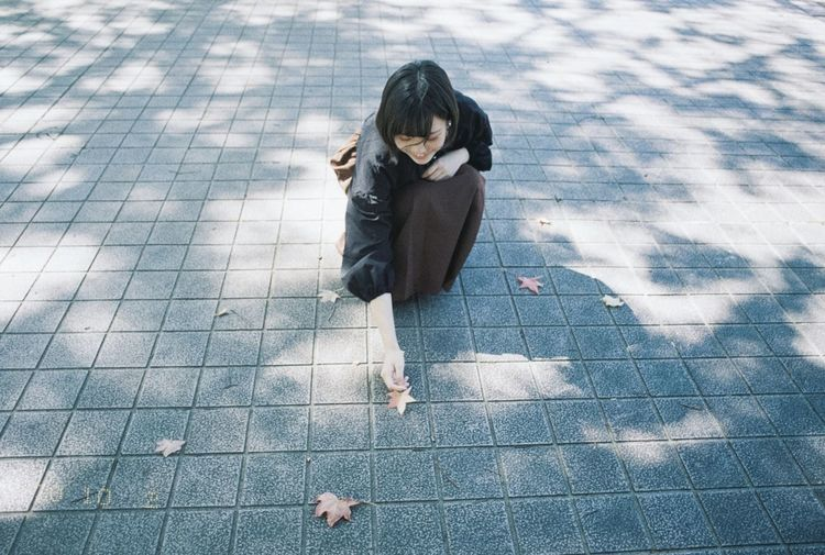 High angle view of woman sitting on footpath