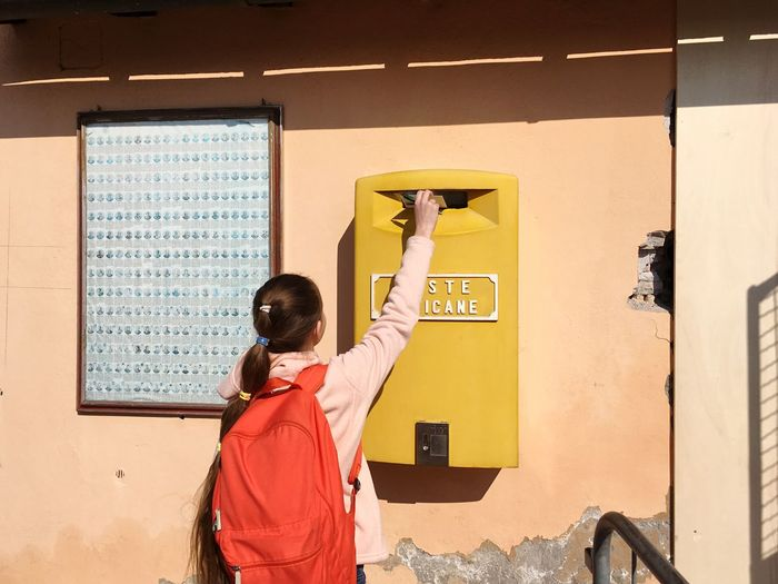 Rear view of girl putting letter in mailbox on wall