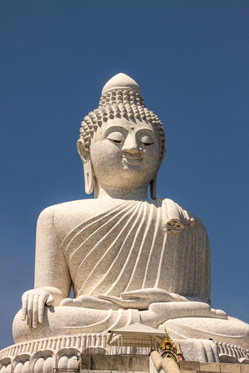 Low angle view of statue against temple against clear blue sky