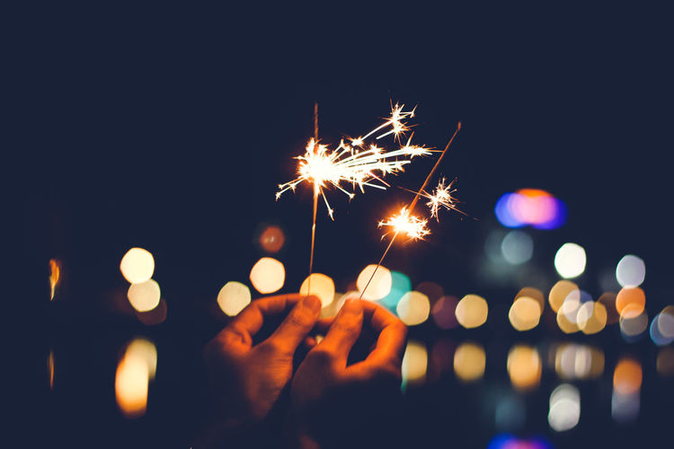 Cropped hands holding sparklers against defocused lights at night