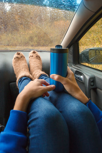 Low section of woman holding bottle sitting in car