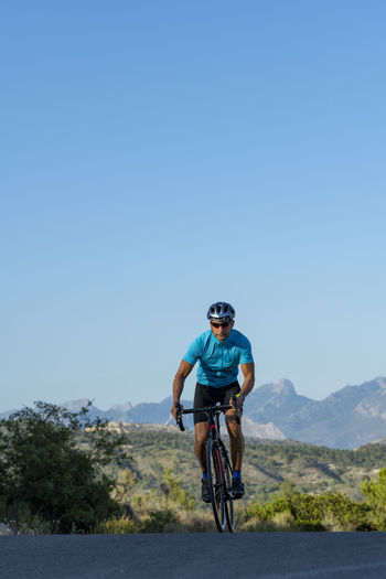 Man riding bicycle on mountain against blue sky