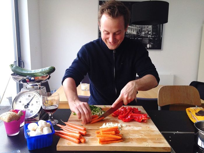 Happy chef chopping vegetables on cutting board