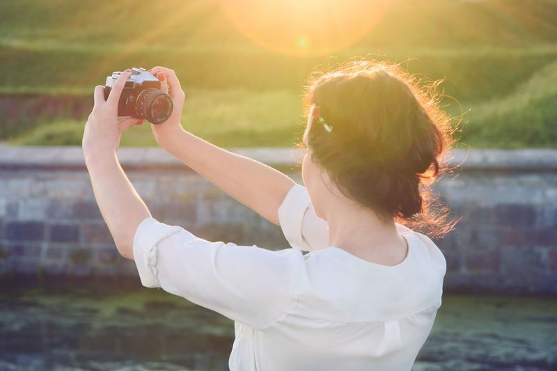 Rear View Of Girl Taking A Selfie By Canal