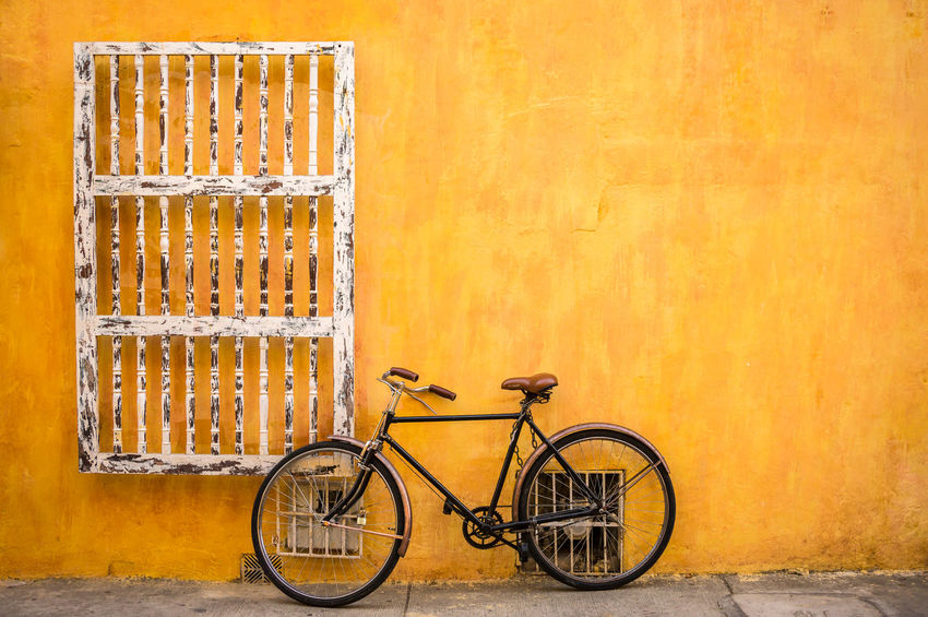 A classic bicycle parked in front of a bright yellow wall in Cartagena, Colombia. Antique Bicycle Bicycle Parking Bright Canary Yellow Cartagena Cheerful Classic Colombia Day Excitement Negative Space No People Outdoors Plaster S Street Summer Tourism Transportation Urban Urban Transportation Wall Yellow