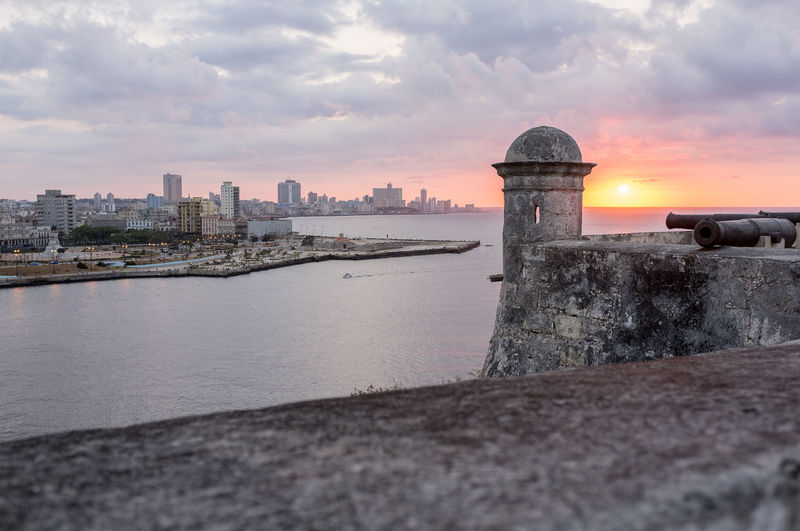 View of central Havana at sunset from the La Cabaña fort. Architecture Cityscapes Cloudy Cuba Havana La Cabaña No People Orange Color Sunset Tourism Travel Travel Destinations