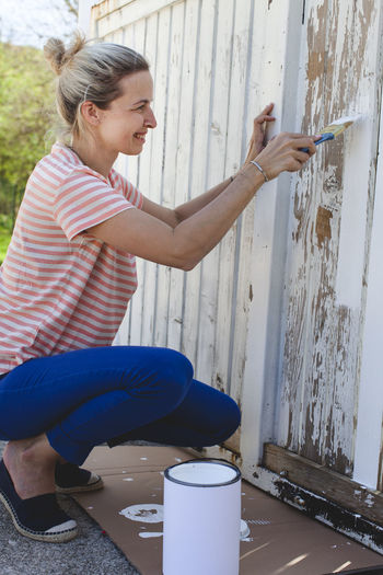 Smiling woman painting fence at yard