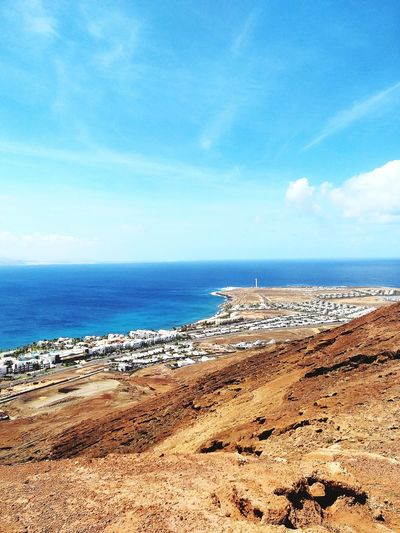 SPAIN Lanzarote Canary Islands Water Sea Beach Sand Blue Sky Horizon Over Water Cloud - Sky Close-up Pebble Beach Coast Rushing Pebble Seashore Shore Seaside Surf Rock Formation Water Vehicle Rock Driftwood Calm Groyne Natural Arch Stack Rock Evening Surfer