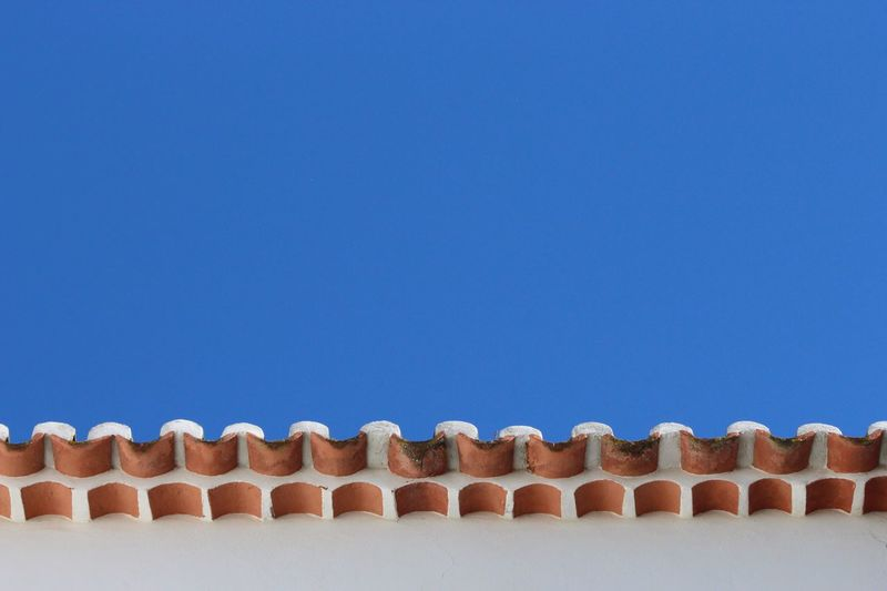 Close-up of wall and roof against clear blue sky