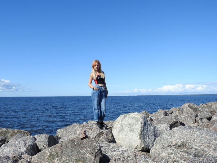 Full length of girl standing on rock against sea and sky