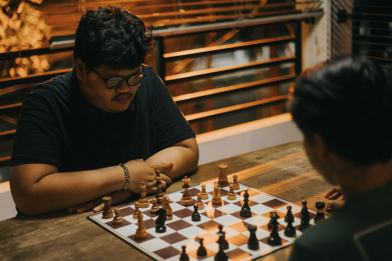 Man playing with chess in background
