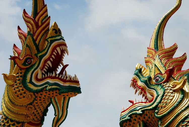 Low Angle View Of Colorful Dragon Sculptures Against Sky
