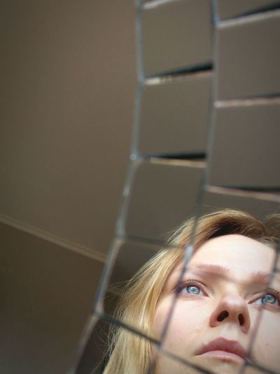 Close-up of thoughtful woman looking away reflecting on glass table