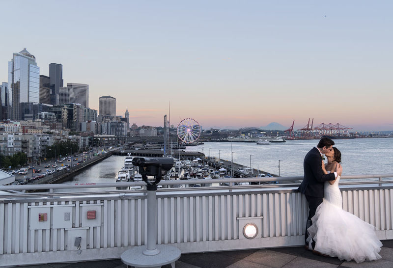 Just married couple posing at sunset with the Seattle skyline and Mount Rainier in the distance. Architecture Bonding Bride Bridge - Man Made Structure Building Exterior Built Structure City Cityscape Dress Full Length Lifestyles Love Men Real People Sea Sky Sunset Togetherness Two People Water Wedding Wedding Dress Women Young Women