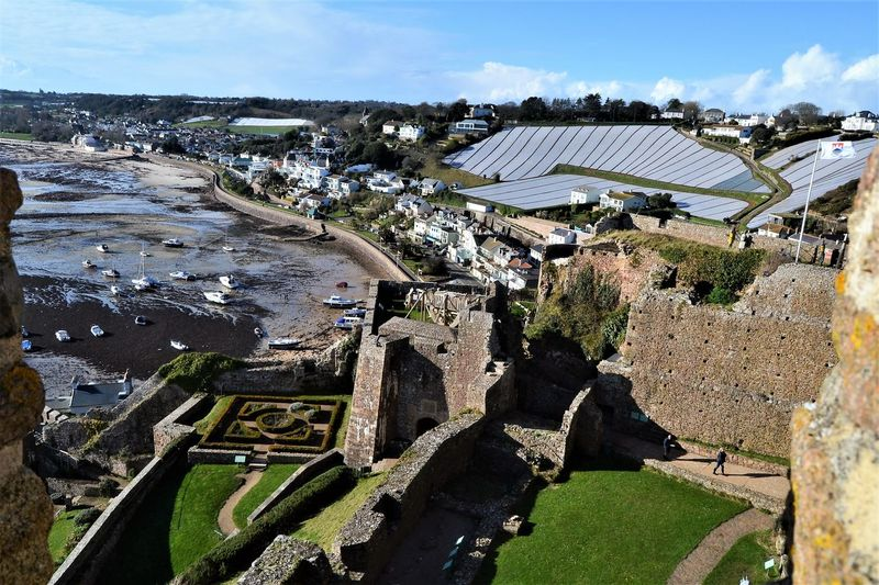 """Gorey, the home of the """"Jersey Royals"""" with the potato farm seen at the top right being kept under poly-carbonate wrap in the winter months. Viewed from the top of Gorey Castle, Jersey, Channel Islands Jersey Royals Potato Field Architecture Building Building Exterior Built Structure Cloud - Sky Day Environment Farming Gorey High Angle View Landscape Nature No People Outdoors Plant Ruined Sky Sunlight Travel Travel Destinations Tree Water"""