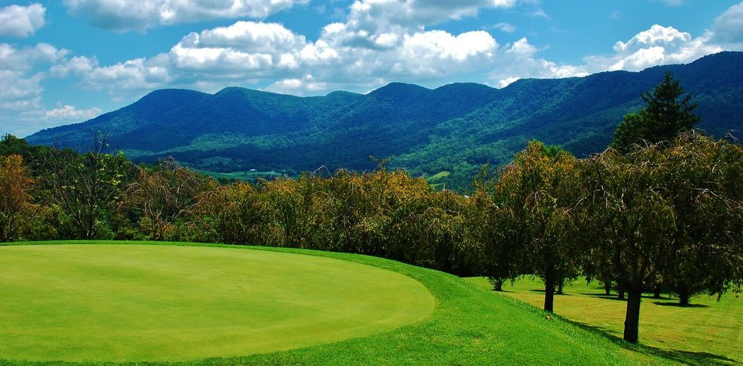 On the Green Golf Course Green Beauty In Nature Cloud - Sky Day Golf Golf Course Grass Green - Golf Course Green Color Mountain Nature No People Outdoors Scenics Sky Sport Tranquility Tree