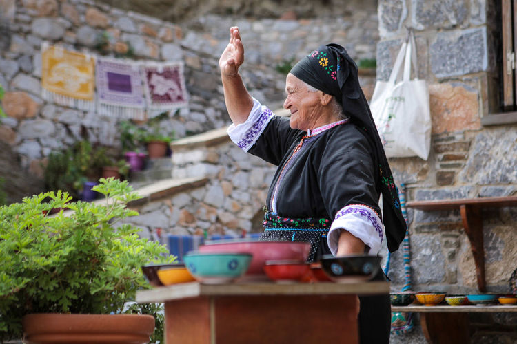Old woman in traditional Greek folk dress sells souvenirs in the Olympos village Folk Dress Folk Art  Old Woman Three Quarter Length Occupation Waist Up Brick Wall Leisure Activity Brick Women Container Day Mature Adult Wall - Building Feature Casual Clothing Lifestyles Wall Adult Side View Real People One Person