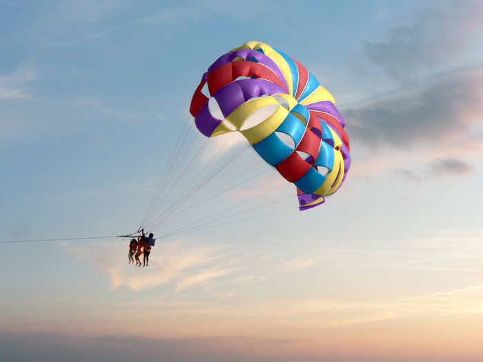 Low angle view of people parasailing against sky during sunset