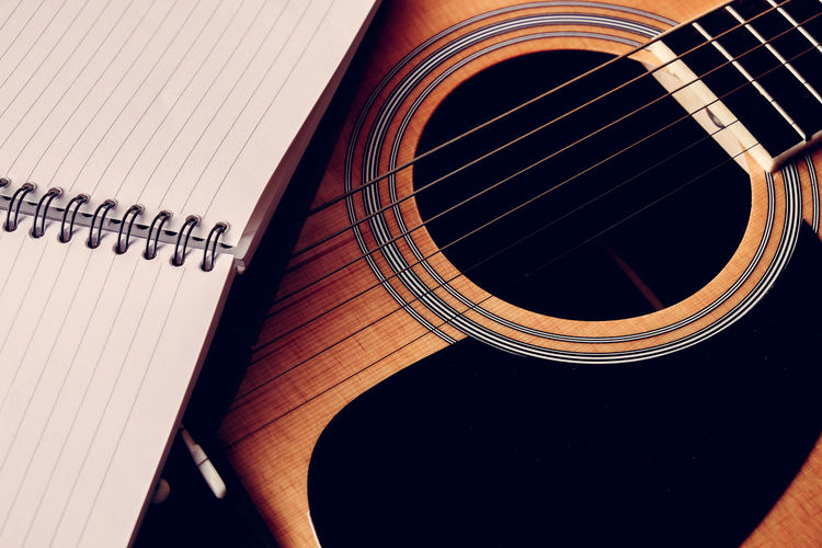 High angle view of spiral notebook on guitar