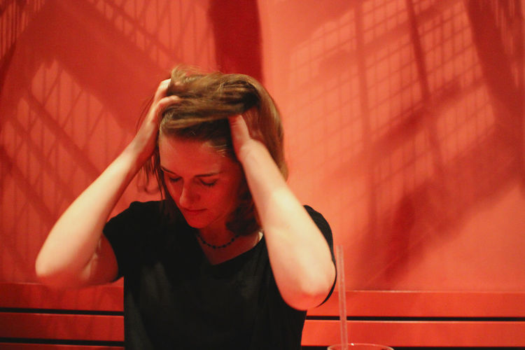 Beautiful Blond Woman Suffering From Headache Against Red Wall