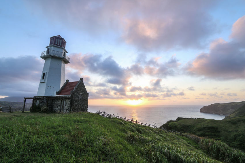 Mahatao Lighthouse against sunrise at Batanes Island, Philippines Hope Mahatao New Philippines Shine Architecture Batanes Beauty In Nature Beginning Dawn Day Grass Guidance Horizon Landscape Lighthouse Nature Outdoors Scenics Sky Sunrise Sunset Tower Water