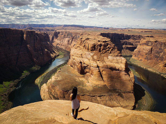Rear view of woman standing at horseshoe bend