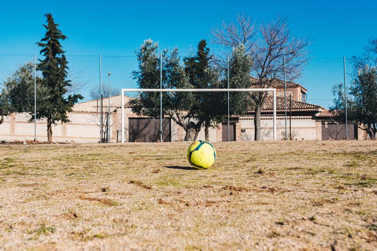 Soccer ball on grass against blue sky