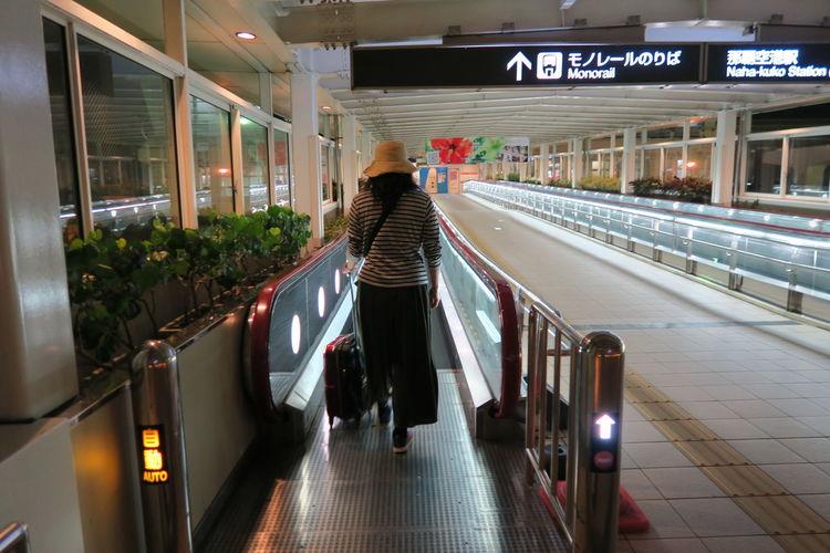Rear view of woman walking on illuminated railway station