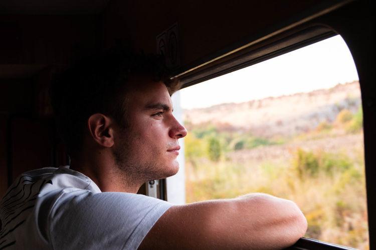 Close-up of man looking through car window