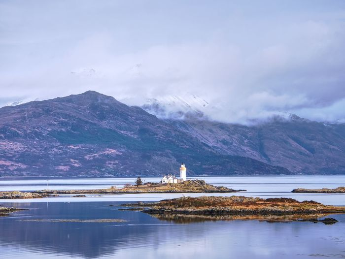 Isle ornsay lighthouse built on a small isle located on ferry route. low water. snowy mountain