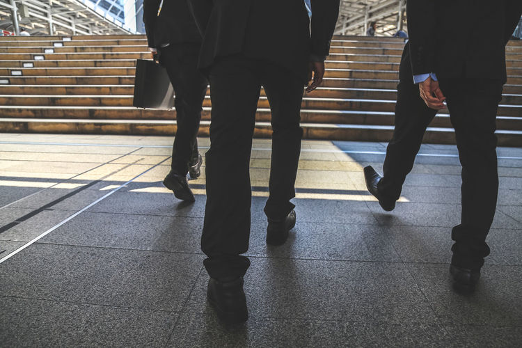 Low section of businessmen walking towards steps