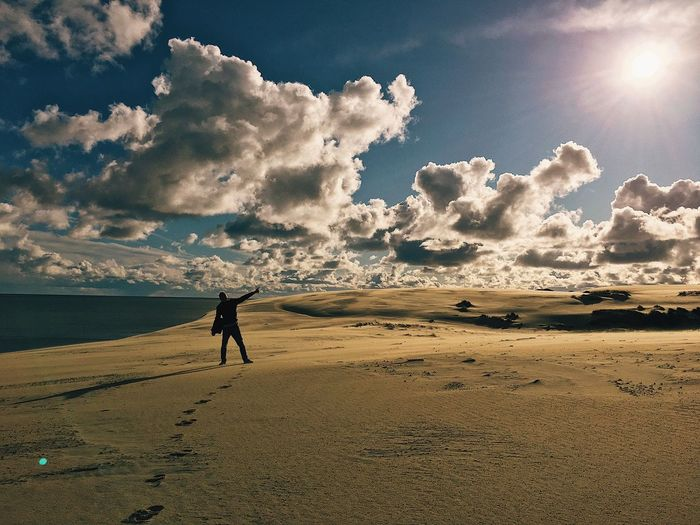 Man standing at beach against cloudy sky