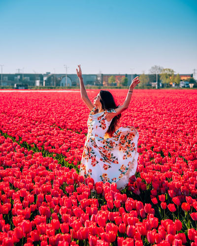 Woman standing by red flowering plants against sky
