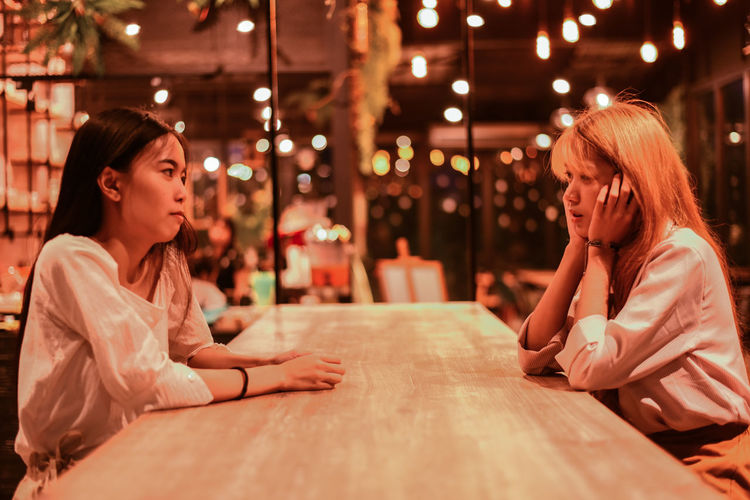 Female friends talking while sitting at table in restaurant