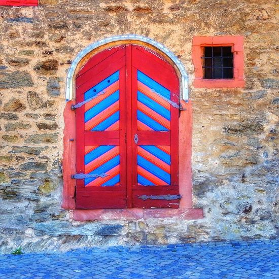 Red and blue patterns on a wooden door in a brick wall facade Façade Brick Wall Pattern Blue Color Red Color Window Built Structure Architecture Building Exterior Wall - Building Feature Red Window Building No People Closed Door Wall Entrance Outdoors Blue Wood - Material Wall