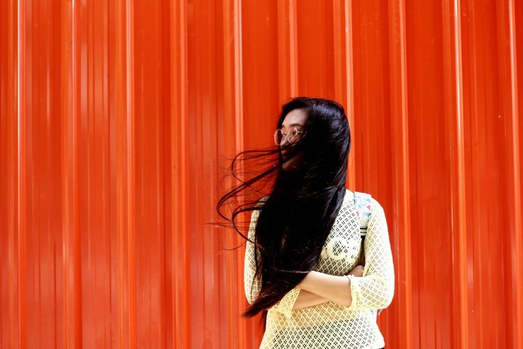 Woman with tousled hair standing against orange wall