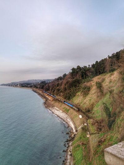 Aerial view of cliff by sea against cloudy sky