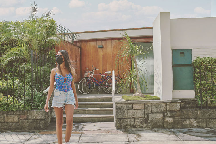 Woman standing by swimming pool in yard against house