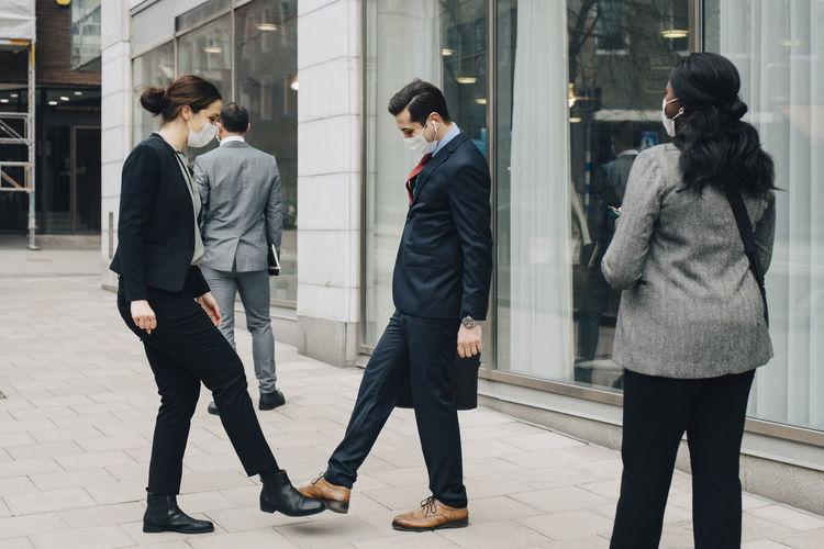 Friends walking on footpath in city