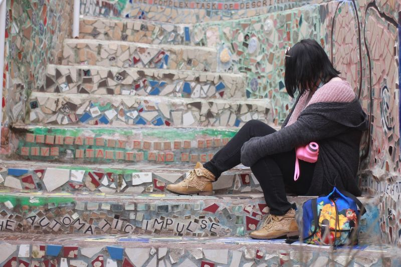 Young woman sitting at the steps of magic gardens Philadelphia Colorful Tiles Emotional Sombre Creative One Person Architecture Lifestyles Real People Adult Built Structure Sitting Day Leisure Activity Wall - Building Feature Women Hair Full Length Casual Clothing Rear View Staircase Clothing Hairstyle Warm Clothing