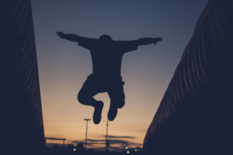 Rear View Of Silhouette Man Jumping Against Sky During Sunset