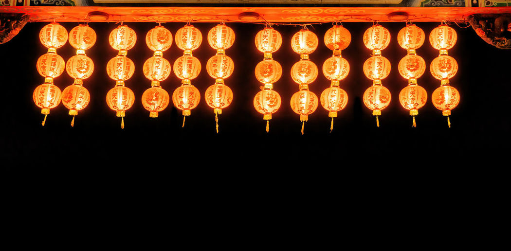 Illuminated lanterns hanging in the dark