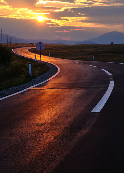 Road by street against sky during sunset