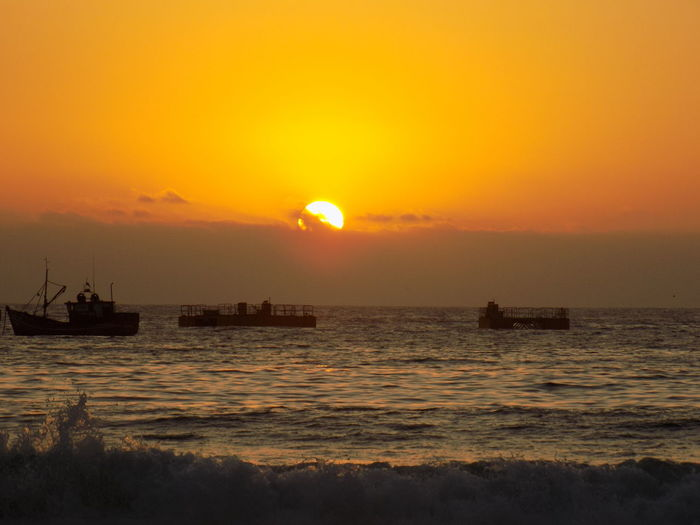 Boats in the sea Beauty In Nature Freight Transportation Horizon Horizon Over Water Mode Of Transportation Nature Nautical Vessel No People Orange Color Outdoors Scenics - Nature Sea Silhouette Sky Sun Sunset Tranquil Scene Tranquility Transportation Water