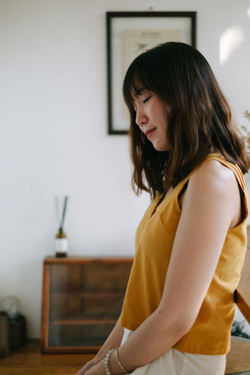 Woman looking away while standing at home