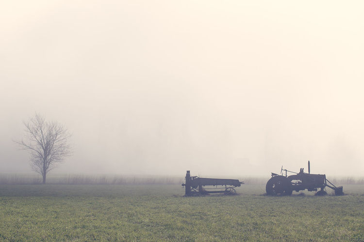Tractor on field against sky during foggy weather