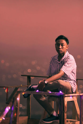 Young man sitting on chair against cityscape during sunset