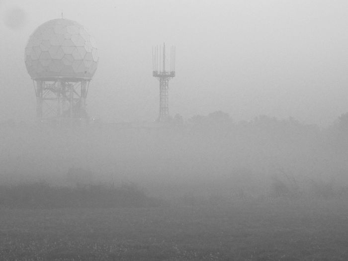Tower on field against sky during foggy weather